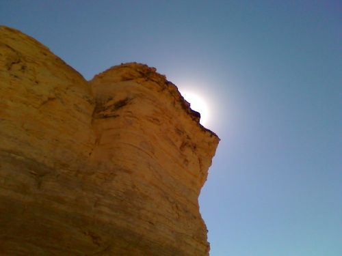 The sun behind a formation at Monument Rocks